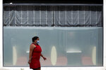 A woman wearing a face mask walks past a hotel in downtown Lisbon, Saturday, July 10, 2021. Germany eased its recent strict restrictions on travel to Portugal, which had disheartened the Portuguese tourism sector. (AP Photo/Armando Franca)