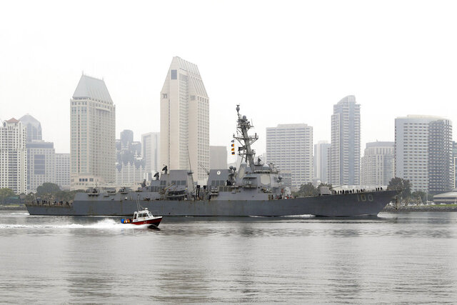 In this April 28, 2020, photo, the USS Kidd passes downtown San Diego as it returns to Naval Base San Diego, seen from Coronado, Calif. Lessons learned from a coronavirus outbreak aboard the aircraft carrier USS Theodore Roosevelt played a central role in limiting damage when the virus hit the USS Kidd at sea (AP Photo/Gregory Bull)