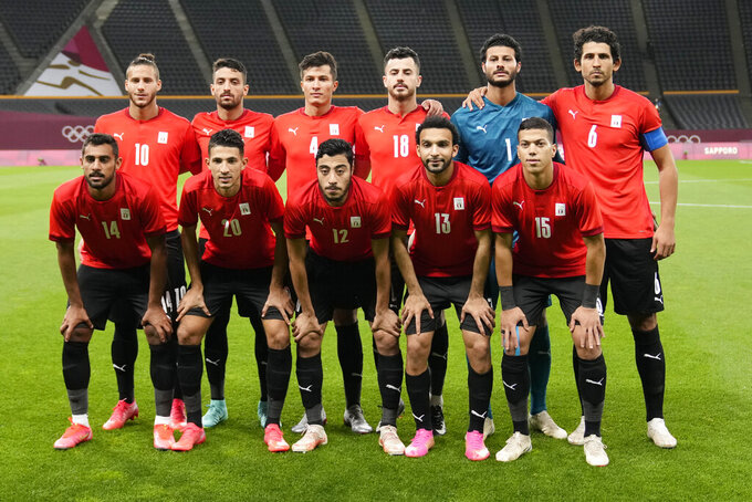 Players of Egypt pose for the group photo prior to their men's soccer match against Spain at the 2020 Summer Olympics, Thursday, July 22, 2021, in Sapporo, Japan. (AP Photo/SIlvia Izquierdo)