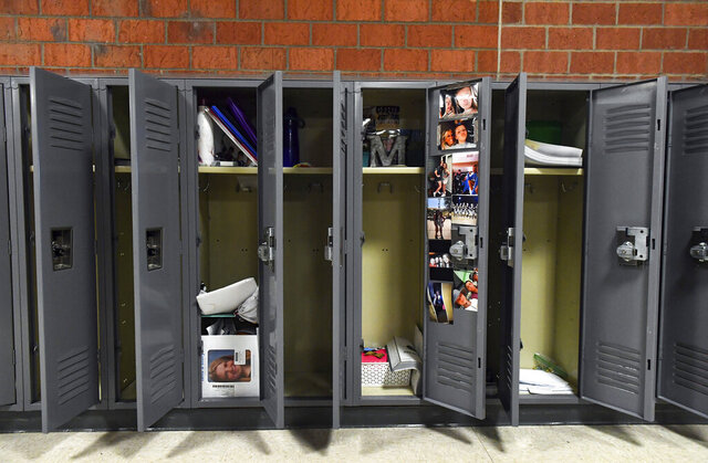 In this Monday, May 11, 2020 photo, lockers full of students' belongings stand open in the empty hallways of Memorial Middle School in Sioux Falls, S.D. (Erin Bormett/The Argus Leader via AP)