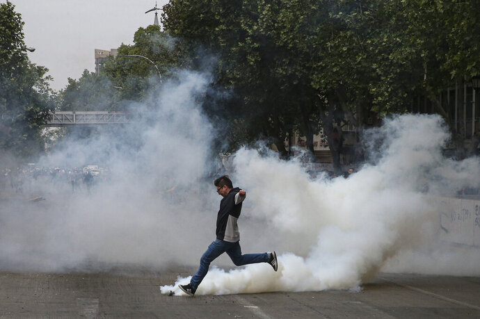 A protester kicks a tear gas canister launched by police during a protest in Santiago, Chile, Saturday, Oct. 19, 2019. The protests started on Friday afternoon when high school students flooded subway stations, jumping turnstiles, dodging fares and vandalizing stations as part of protests against a fare hike, but by nightfall had extended throughout Santiago with students setting up barricades and fires at the entrances to subway stations, forcing President Sebastian Pinera to announce a state of emergency and deploy the armed forces into the streets. (AP Photo/Esteban Felix)