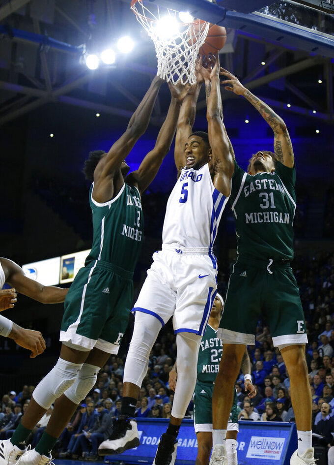 Buffalo guard CJ Massinburg (5) goes up against Eastern Michigan defenders during the first half of an NCAA college basketball game, Friday, Jan. 18, 2019, in Buffalo N.Y. (AP Photo/Jeffrey T. Barnes)