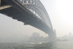 Smoke haze hangs over the Sydney Harbour Bridge in Sydney, Thursday, Nov. 21, 2019. The annual Australian fire season, which peaks during the Southern Hemisphere summer, has started early after an unusually warm and dry winter. (AP Photo/Rick Rycroft)
