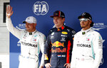 Red Bull driver Max Verstappen of the Netherland's, center, Mercedes driver Valtteri Bottas of Finland, left, and Mercedes driver Lewis Hamilton of Britain stand on the podium after qualification for the Hungarian Formula One Grand Prix at the Hungaroring racetrack in Mogyorod, northeast of Budapest, Hungary, Saturday, Aug. 3, 2019. Red Bull driver Max Verstappen of the Netherland's will take his first career pole position in the Hungarian Formula One Grand Prix on Sunday. (AP Photo/Laszlo Balogh)