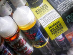 FILE- This Sept. 16, 2019 file photo shows flavored vaping solutions in a window display at a vape and smoke shop in New York. On Thursday, Jan. 2, 2020, the Trump administration announced that it will prohibit fruit, candy, mint and dessert flavors from small, cartridge-based e-cigarettes that are popular with high school students. But menthol and tobacco-flavored e-cigarettes will be allowed to remain on the market.The flavor ban will also entirely exempt large, tank-based vaping devices, which are primarily sold in vape shops that cater to adult smokers. (AP Photo/Bebeto Matthews, File)