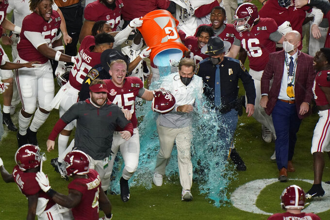 Alabama head coach Nick Saban is soaked in a sports drink after their win against Ohio State in an NCAA College Football Playoff national championship game, Monday, Jan. 11, 2021, in Miami Gardens, Fla. Alabama won 52-24. (AP Photo/Wilfredo Lee)