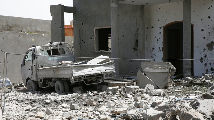 FILE - In this June 15, 2019, file photo, a vehicle and structure is damaged from fighting in the region of Tajoura, east of the Libyan capital Tripoli. The battle between rival militias for the Libyan capital has killed more than 1,000 people since it began in April, the U.N. said Tuesday, a grim milestone in a stalemated conflict partly fueled by regional powers. (AP Photo/Hamza Turkia, File)