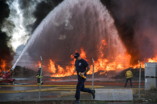 A plastic pallet fire rages at a tomato processing plant in Stockton, Calif., on Tuesday, May 26, 2020. Stockton Fire said on social media that roughly 1.5 acres of plastic pallets were burning Tuesday and drivers are asked to avoid the area. No one has been injured although one firefighter was taken to a hospital with heat exhaustion. (Clifford Oto/The Stockton Record via AP)