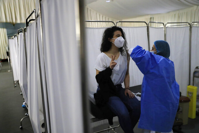 A woman flashes a victory sign as she receives the Pfizer-BioNTech COVID-19 vaccine during a nationwide vaccination campaign, at the Saint George Hospital, in Beirut, Lebanon, Tuesday, Feb. 16, 2021. Lebanon launched its inoculation campaign after receiving the first batch of the vaccine — 28,500 doses from Brussels with more expected to arrive in the coming weeks. (AP Photo/Hussein Malla)