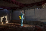A Kashmir man in personal protective equipment sprays disinfectant to sanitize a wedding tent on the outskirts of Srinagar, Indian controlled Kashmir, Thursday, Sept. 17, 2020. The coronavirus pandemic has changed the way people celebrate weddings in Kashmir. The traditional week-long feasting , elaborate rituals and huge gatherings have given way to muted ceremonies with a limited number of close relatives attending. With restrictions in place and many weddings cancelled, the traditional wedding chefs have little or no work. The virus has drastically impacted the life and businesses in the region. (AP Photo/ Dar Yasin)
