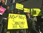 FILE - In this April 14, 2017, file photo, protesters hold up signs outside a courthouse in San Francisco. A federal appeals court has given the Trump administration a rare legal win in its efforts to crack down on sanctuary cities. In a 2-1 decision Friday, July 12, 2019, the 9th U.S. Circuit Court of Appeals said the Justice Department was within its rights to give priority status for multimillion-dollar community policing grants to departments that agree to cooperate with immigration officials.  (AP Photo/Haven Daley, File)