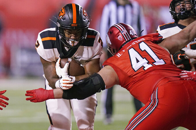 Utah defensive tackle Hauati Pututau (41) tackles Oregon State running back Calvin Tyler Jr. (2) during the first half of an NCAA college football game Saturday, Dec. 5, 2020, in Salt Lake City. (AP Photo/Rick Bowmer)