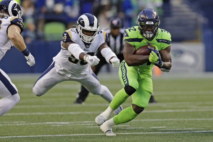 Seattle Seahawks running back Chris Carson, right, carries as Los Angeles Rams outside linebacker Samson Ebukam, left, leaps to attempt a tackle during the first half of an NFL football game Thursday, Oct. 3, 2019, in Seattle. (AP Photo/Stephen Brashear)