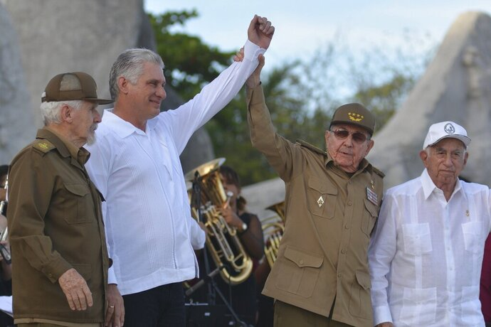 FILE - In this July 26, 2019 file photo, Cuba's President Miguel Diaz-Canel, second left, and former President Raul Castro, raise their arms in unison during an event celebrating Revolution Day, accompanied by Commander of the Cuban Revolution Ramiro Valdes, left, and Jose Ramon Machado Ventura, second secretary of the Central Committee, in Bayamo, Cuba. Cuba's top legislative body will no longer include members of the country's historical generation of former rebels, part of a broader political reform that started to go into effect on Thursday, Oct. 10, 2019. (Omara Garcia/Agencia Cubana de Noticias via AP File)