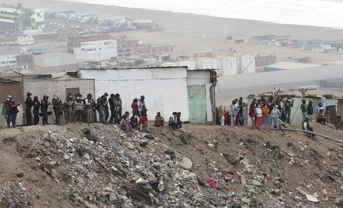 Squatters watch as police tear down their shacks in their recently formed settlement on a hilltop in the Villa El Salvador neighborhood, which had been occupied by mostly people who can no longer pay their rent because of restrictions on economic activity aimed at limiting the spread of COVID-19, in Lima, Peru, Wednesday, April 28, 2021. (AP Photo/Martin Mejia)