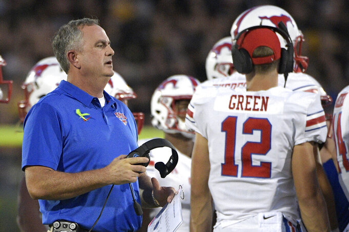 FILE - In this Saturday, Oct. 6, 2018 file photo, SMU head coach Sonny Dykes, left, talks to his players during a timeout in the first half of an NCAA college football game against Central Florida in Orlando, Fla. Best to expect the unexpected in the AAC. The league has been fertile ground for fast turnarounds since it rose from the ashes of the old Big East in 2013. SMU under second-year coach Sonny Dykes was in the thick of the West Division race last season until losing its last two. The Mustangs add former Texas quarterback Shane Buechele, among several transfers who could give SMU more staying power. (AP Photo/Phelan M. Ebenhack, File)