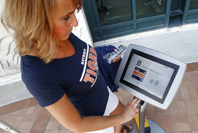 FILE - In this July 25, 2017, file photo, Jacquelyn Klimsza, of Fruitport, Mich., scans her fingerprints at a CLEAR biometric system outside Comerica Park before a baseball game between the Detroit Tigers and Kansas City Royals in Detroit. Screening technology that scans a user's eyes, face or fingerprint has multiplied around the world in recent years. (AP Photo/Paul Sancya, File)