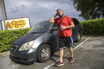Jeff Lello stands next to the van in which he lives, in the parking lot of a Cracker Barrel restaurant, since being laid off due to the coronavirus pandemic, Friday, Aug. 21, 2020, in Orlando, Fla. Lello is one of an estimated 20 million Americans living paycheck to paycheck, spending more than 30% of their income on rent, who are likely to experience homelessness at some point, according to the National Coalition for the Homeless. (AP Photo/Phelan M. Ebenhack)