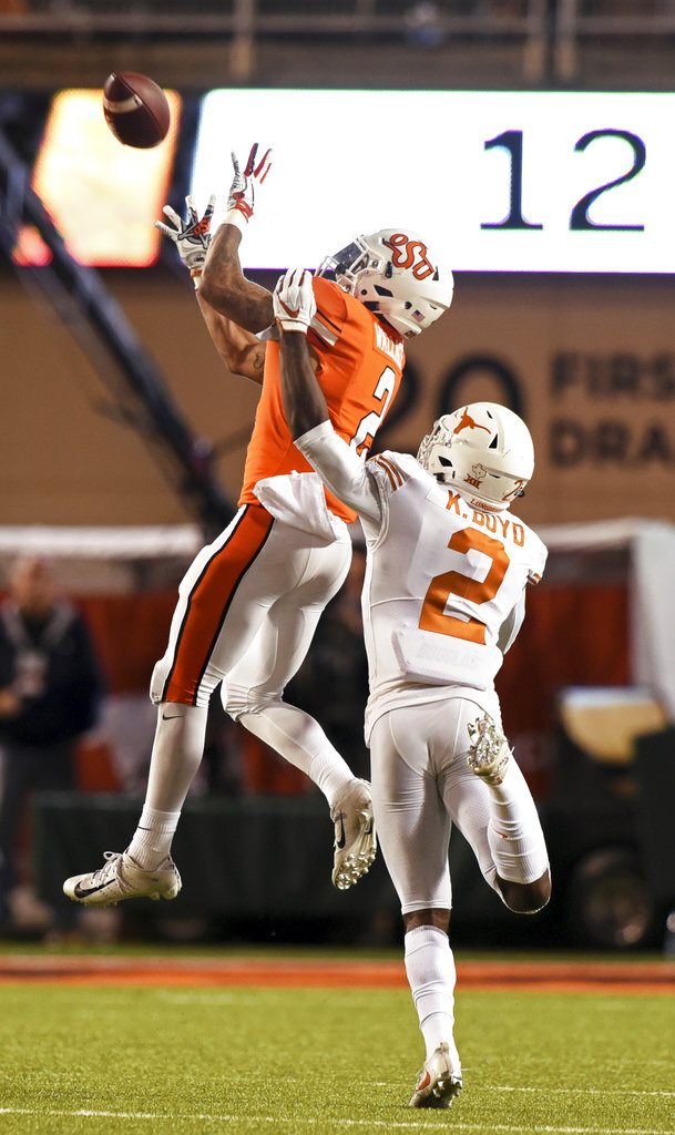 Oklahoma State wide receiver Tylan Wallace, left, catches a pass over pressure from Texas defensive back Kris Boyd in the second half of an NCAA college football game in Stillwater, Okla., Saturday, Oct. 27, 2018. Wallace scored 2 touchdowns in the Oklahoma State 38-35 win over Texas. (AP Photo/Brody Schmidt)