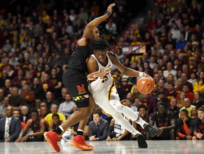Minnesota's Daniel Oturu (25) drives toward the basket asMaryland forward Donta Scott defends during the first half of an NCAA college basketball game Wednesday, Feb. 26, 2020, in Minneapolis. (AP Photo/Hannah Foslien)