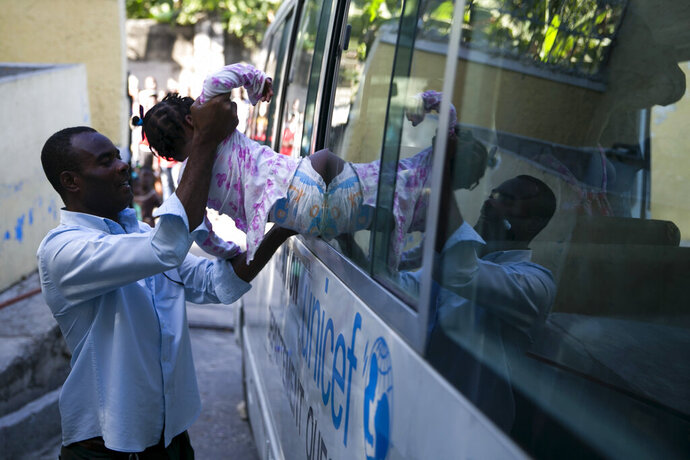 A state worker puts a child into a social services bus after her removal from another branch of the Orphanage of the Church of Bible Understanding, in the Kenscoff area outside Port-au-Prince, Haiti, Friday, Feb. 14, 2020. A fire swept through a nearby orphanage also run by the Pennsylvania-based nonprofit group, killing 15 children, officials said Friday. (AP Photo/Dieu Nalio Chery)