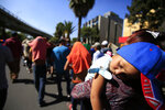 A sleeping Honduran girl is carried as a group of Central American migrants, representing the thousands participating in a caravan trying to reach the U.S. border, undertake an hours-long march to the office of the United Nations' humans rights body in Mexico City, Thursday, Nov. 8, 2018. Members of the caravan which has stopped in Mexico City demanded buses Thursday to take them to the U.S. border, saying it tis too cold and dangerous to continue walking and hitchhiking.(AP Photo/Rebecca Blackwell)