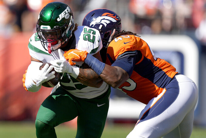 New York Jets running back Ty Johnson (25) is tackled by Denver Broncos linebacker A.J. Johnson (45) during the first half of an NFL football game, Sunday, Sept. 26, 2021, in Denver. (AP Photo/David Zalubowski)