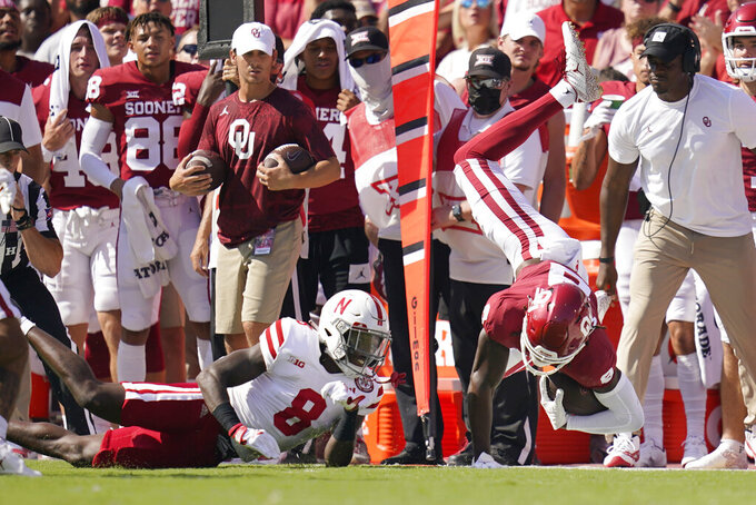 Oklahoma wide receiver Michael Woods II, right, is upended by Nebraska safety Deontai Williams (8) in the first half of an NCAA college football game, Saturday, Sept. 18, 2021, in Norman, Okla. (AP Photo/Sue Ogrocki)