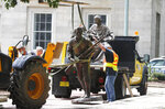 Crews add The Henry Wyatt Monument to a truck after removing them from the North Carolina State Capitol in Raleigh, N.C., Saturday, June 20, 2020. crews removed one statue dedicated to the women of the Confederacy, and another placed by the United Daughters of the Confederacy honoring Henry Wyatt, the first North Carolinian killed in battle in the Civil War. Both statues stood for over a century. It was not immediately clear who ordered the removals.  (Ethan Hyman/The News & Observer via AP)