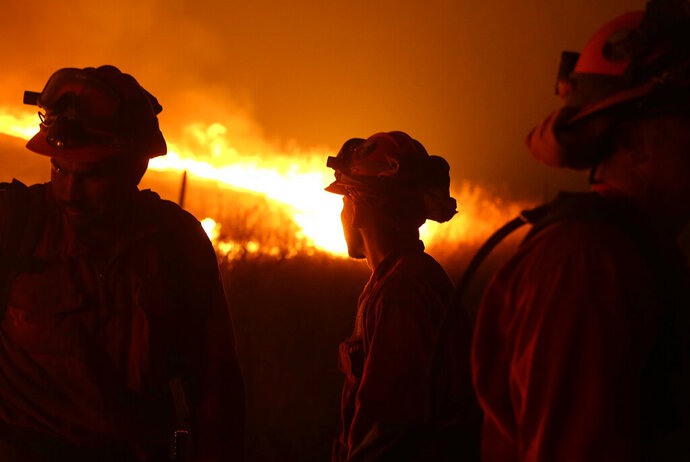 FILE - In this Sept. 12, 2015 file photo, California Department of Corrections and Rehabilitation inmates stand guard as flames from the Butte Fire approach a containment line near San Andreas, Calif. California Gov. Gavin Newsom is stepping up pressure on Pacific Gas and Electric to fork over billions more in cash to pay thousands of people whose homes burned in wildfires that drove the utility into bankruptcy. The rising tensions were expected to surface at a hearing Wednesday, Nov. 13, 2019, that has been abruptly postponed by a week. (AP Photo/Rich Pedroncelli, File)