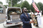 A musician plays music near the hearse carying the casket of Rayshard Brooks, Tuesday, June 23, 2020, in Atlanta. The funeral for Brooks was held today. Brooks died after being fatally shot by an Atlanta police officer. (AP Photo/John Bazemore)