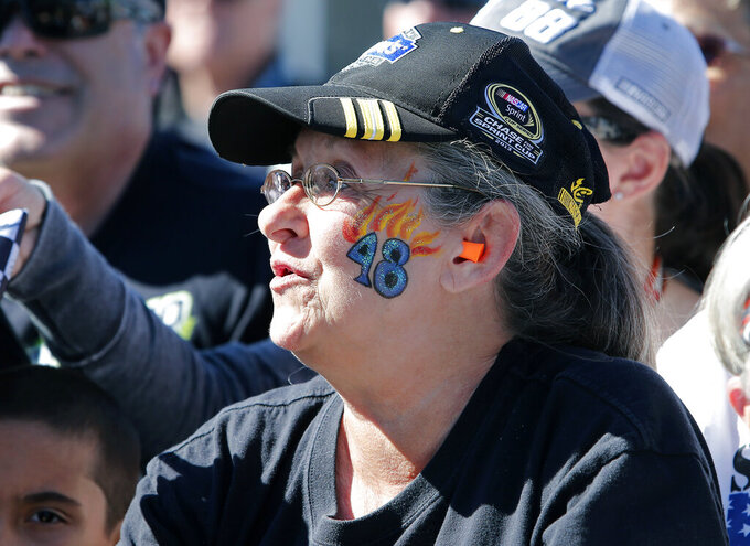 A Jimmie Johnson fan reacts to seeing her favorite driver prior to the start of the NASCAR Cup Series auto race at ISM Raceway, Sunday, March 10, 2019, in Avondale, Ariz. (AP Photo/Ralph Freso)
