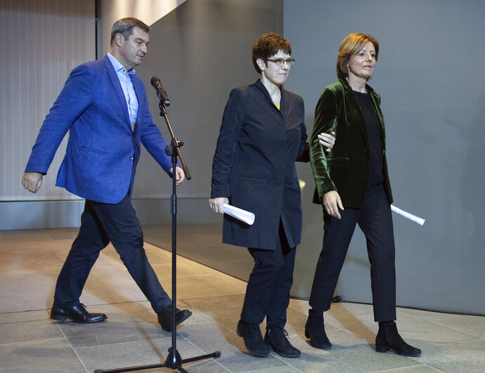 The chairmen of Germany's governing parties, Markus Soeder (CSU), Annegret Kramp-Karrenbauer (CDU) and Malu Dreyer (SPD), from left, arrive to a press conference in Berlin, Germany, to confirm agreement on a reform of the country's pension system, setting aside an ideological dispute that had threatened to unravel the coalition government, Sunday, Nov. 10, 2019. (Soeren Stache/dpa via AP)