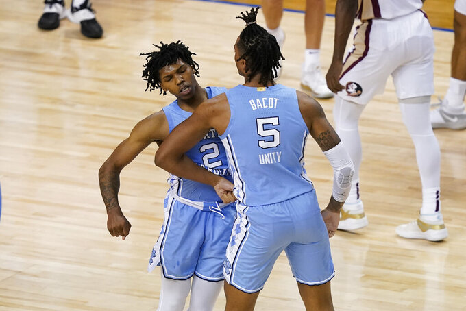 North Carolina guard Caleb Love (2) and teammate forward Armando Bacot (5) celebrate a play during the second half of an NCAA college basketball game against Florida State in the semifinal round of the Atlantic Coast Conference tournament in Greensboro, N.C., Friday, March 12, 2021. (AP Photo/Gerry Broome)