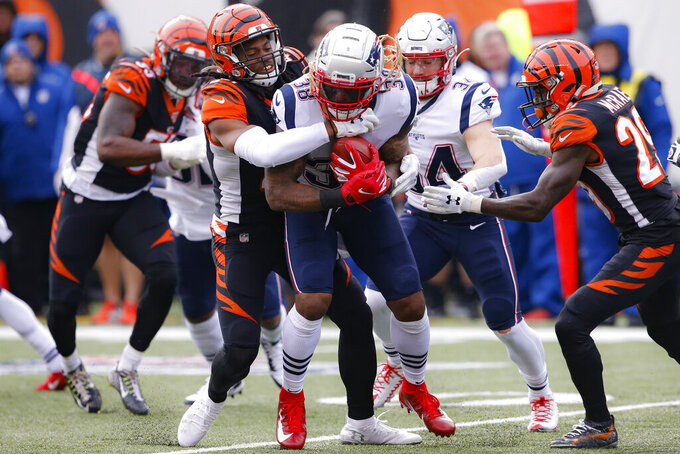 New England Patriots running back Brandon Bolden (38) is tackled by Cincinnati Bengals cornerback Darius Phillips, center left, in the first half of an NFL football game, Sunday, Dec. 15, 2019, in Cincinnati. (AP Photo/Gary Landers)