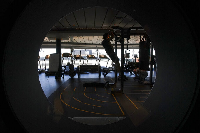 A man exercises in a gym on the MSC Grandiosa cruise ship in Civitavecchia, near Rome, Wednesday, March 31, 2021. MSC Grandiosa, the world's only cruise ship to be operating at the moment, left from Genoa on March 30 and stopped in Civitavecchia near Rome to pick up more passengers and then sail toward Naples, Cagliari, and Malta to be back in Genoa on April 6. For most of the winter, the MSC Grandiosa has been a lonely flag-bearer of the global cruise industry stalled by the pandemic, plying the Mediterranean Sea with seven-night cruises along Italy's western coast, its major islands and a stop in Malta. (AP Photo/Andrew Medichini)