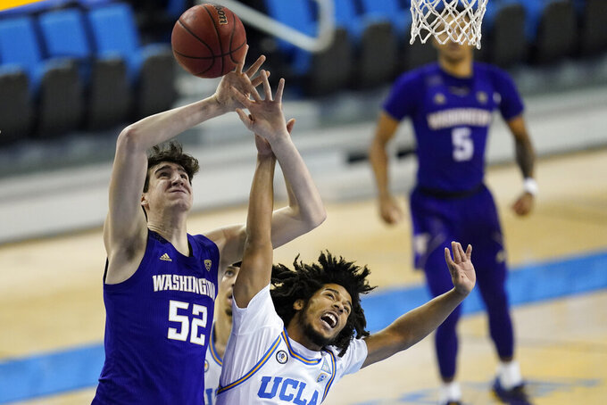 UCLA guard Tyger Campbell, right, breaks up a shot by Washington center Riley Sorn (52) during the first half of an NCAA college basketball game Saturday, Jan. 16, 2021, in Los Angeles. (AP Photo/Ashley Landis)