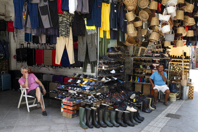 Two vendors sit outside shops at a market street, in Athens, Thursday, Sep. 3, 2020. Greece has suffered a huge drop in output in the second quarter of the year, plummeting 15.2% on an annual basis, but the government insisted the figures did not worsen the country's annual outlook. (AP Photo/Yorgos Karahalis)