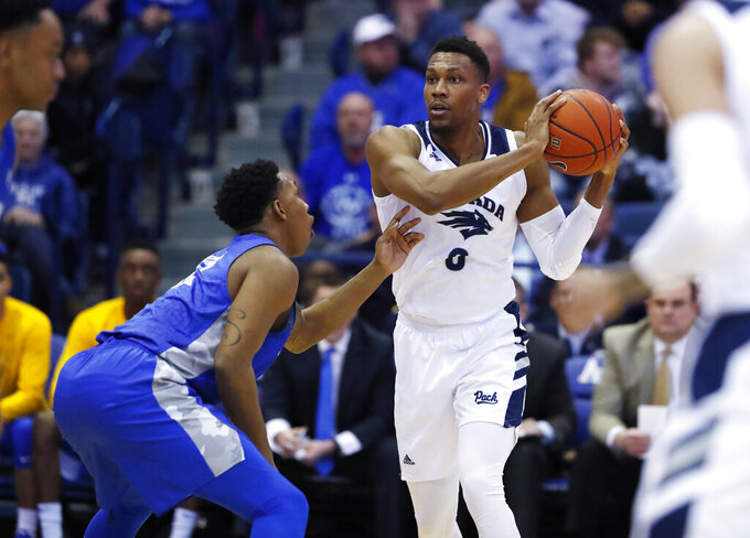Nevada forward Tre'Shawn Thurman, right, looks to pass the ball as Air Force forward Lavelle Scottie defends during the first half of an NCAA college basketball game Tuesday, March 5, 2019, at Air Force Academy, Colo. (AP Photo/David Zalubowski)