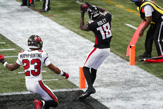 Atlanta Falcons wide receiver Calvin Ridley (18) makes a touchdown catch against Tampa Bay Buccaneers cornerback Sean Murphy-Bunting (23) during the first half of an NFL football game, Sunday, Dec. 20, 2020, in Atlanta. (AP Photo/John Bazemore)