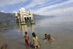 In this Wednesday, April 3, 2019, photo, children play in the water on a beach as a mosque collapsed during the Sept. 28, 2018, earthquake is seen in the background in Palu, Central Sulawesi, Indonesia. The earthquake spawned a large localized tsunami that wiped out coastal areas, while liquefaction caused by the shaking turned entire neighborhoods into rivers of sludge. The disaster killed thousands of people, making it the world's deadliest seismic event in 2018. (AP Photo/Tatan Syuflana)