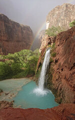 This Wednesday, July 11, 2018 photo released by Benji Xie shows a rainbow over a waterfall on the Havasupai reservation in Supai, Ariz. About 200 tourists were being evacuated Thursday from a campground on tribal land near famous waterfalls deep in a gorge off the Grand Canyon. (Benji Xie via AP)