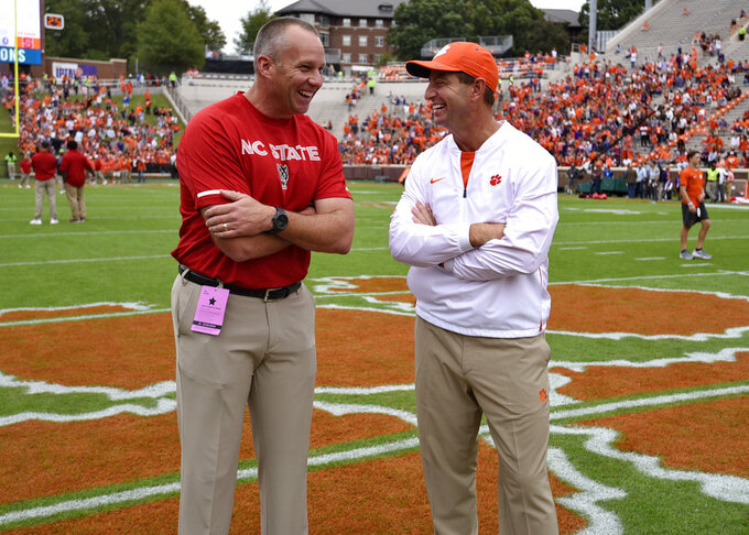 Clemson head coach Dabo Swinney, right, speaks with North Carolina State head coach Dave Doeren before the first half of an NCAA college football game against NC State Saturday, Oct. 20, 2018, in Clemson, S.C. (AP Photo/Richard Shiro)