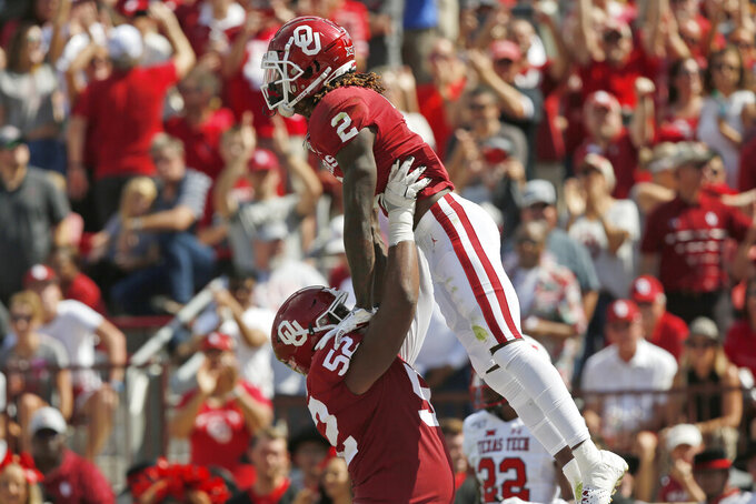 Oklahoma offensive lineman Tyrese Robinson (52) celebrates with teammate CeeDee Lamb (2) follow a touchdown by Lamb in the second quarter of an NCAA college football game against Texas Tech in Norman, Okla., Saturday, Sept. 28, 2019. (AP Photo/Sue Ogrocki)