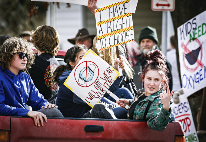 FILE - In this March 9, 2021, file photo, students with signs ride in the back of a pickup truck around Flathead High School to protest the Kalispell School District's face mask requirement in Kalispell, Mont. Amid the coronavirus pandemic, Montana's legislature has passed restrictive laws severely curbing public health's quarantine and isolation powers, increasing local elected officials' power over local health boards, preventing limits on religious gatherings and banning employers — including in health care settings — from requiring vaccinations for covid, the flu or anything else. (Hunter D'Antuono/Flathead Beacon via AP, File)