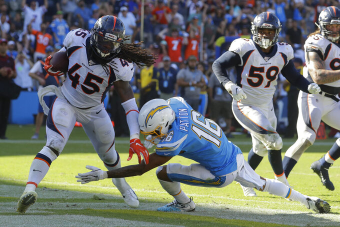 Denver Broncos linebacker A.J. Johnson, left, is tackled by Los Angeles Chargers wide receiver Andre Patton after an interception in the end zone during the second half of an NFL football game Sunday, Oct. 6, 2019, in Carson, Calif. (AP Photo/Alex Gallardo)