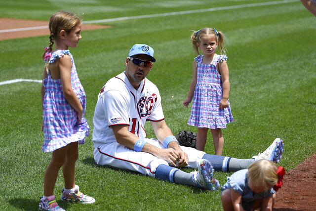 FILE - In this June 16, 2019, file photo, Washington Nationals' Ryan Zimmerman, center, sits on the field with his daughters Mackenzie, left, and Hayden, right, before a baseball game against the Arizona Diamondbacks in Washington. With baseball on hold because of the coronavirus pandemic, Zimmerman occasionally will offer his thoughts via diary entries published by the AP, while waiting for the 2020 season to begin. (AP Photo/Nick Wass, File)