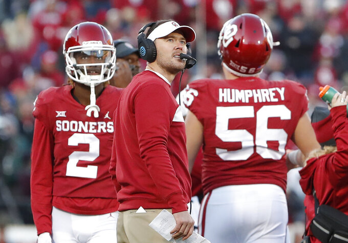 FILE - In this  Saturday, Nov. 10, 2018 file photo, Oklahoma head coach Lincoln Riley, center, watches a replay on the video board during a time out against Oklahoma State in the second half of an NCAA college football game in Norman, Okla. No. 6 West Virginia and No. 12 Oklahoma meet Friday night in Morgantown, W.Va., with the winner earning a berth in the Big 12 championship game next week.  (AP Photo/Alonzo Adams, File)