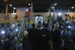 Masked protesters hold up their lit mobile phones as they sing a protest anthem in Hong Kong on Saturday, Oct. 5, 2019. All subway and train services were suspended, lines formed at the cash machines of shuttered banks, and shops were closed as Hong Kong dusted itself off and then started marching again Saturday after another night of rampaging violence decried as