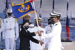 Taiwan's President Tsai Ing-wen, left, presents a flag during the commissioning ceremony of the the domestically made Ta Jiang warship at the Suao naval base in Yilan county, Taiwan, Thursday, Sept. 9, 2021. Taiwan's president oversaw the commissioning of a new domestically made navy warship Thursday as part of the island's plan to boost indigenous defense capacity amid heightened tensions with China. (AP Photo/Chiang Ying-ying)